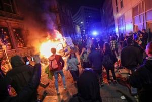 Demonstrators stand near a burning police vehicle.