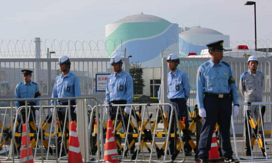 Police officers guard the gate of the Sendai nuclear power plant as protesters rally against the restarting of the reactor.