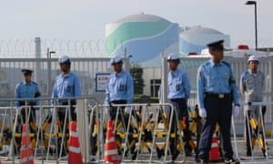 Police officers and security personnel stand in front of the gate of the Kyushu Electric Power Sendai nuclear power plant during a tally of anti-nuclear protesters. The plant restarted its second reactor on Thursday.