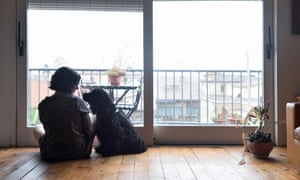 A woman and a dog on the floor of a city flat