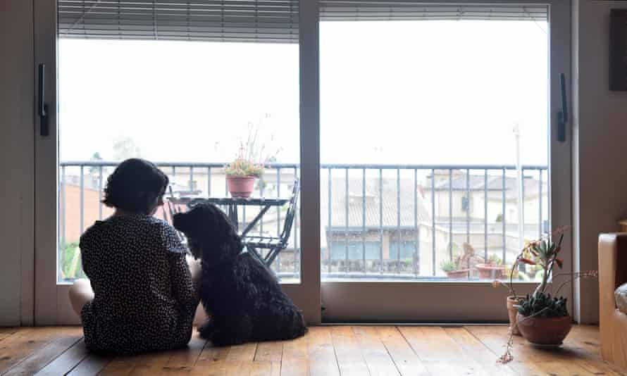 Sad woman sitting and looking out the window with her dog