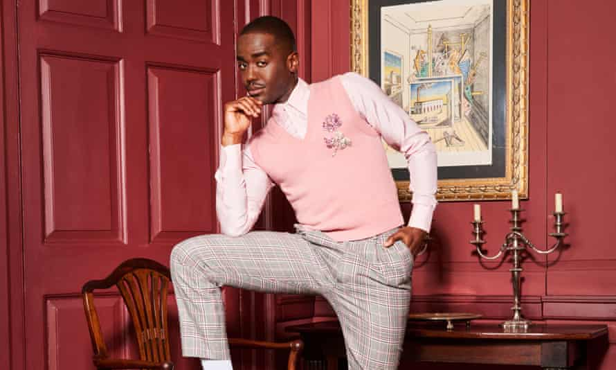 Ncuti Gatwa in grey and pink checked trousers, a pale pink shirt and slightly darker pink sleeveless jumper, one leg up on a chair, in a room with dark pink decor