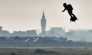 Franky Zapata on his jet-powered flyboard flies past the belfry of the city hall of Calais after he took off from Sangatte, northern France