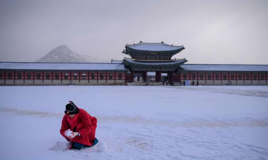 Een gids maakt sneeuwballen op een binnenplaats van paleis Gyeongbokgung, Seoul, Zuid-Korea in 2020.