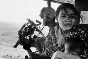 Refugee clutching baby in helicopter gunship