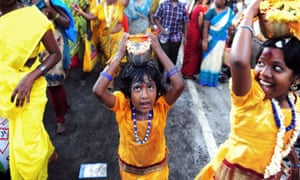 Children carry pots of milk during a religious procession for the Panguni Uthiram festival in Chennai.