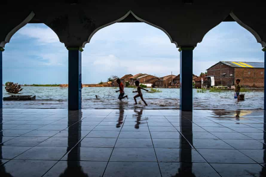 Playing in the flooded yard in front of a mosque.