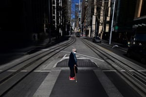 Sydney, Australia. A pedestrian wears a face mask in the city's central business district as stay-at-home orders have been tightened with non-essential retail to close and all construction paused