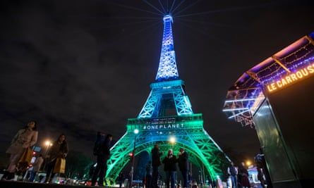 The Eiffel Tower is illuminated by the One Planet Summit colours.