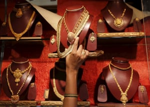 A saleswoman places a gold necklace on a shelf at a showroom in India