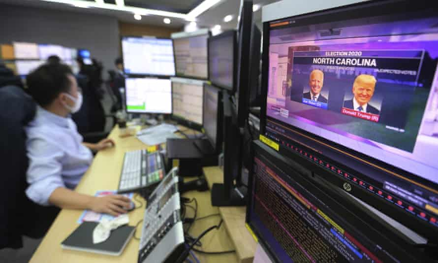 A screen shows live broadcasting of a news programme on the US elections as a currency trader works in a foreign exchange dealing room