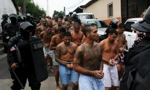 Gang members are guarded by policemen upon their arrival at a prison in El Salvador on 29 March 2016.