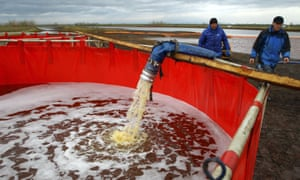Employees of Russia's state-owned oil pipeline monopoly Transneft take part in a clean-up operation.