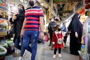 People face masks go shopping in a bazaar in Tehran.