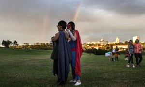 Two participants fix each others costumes as hundreds of other participants gather. The venue of each Secret Sunrise is only revealed the day before to build suspense, and tickets costs 100 rand ($6.30).