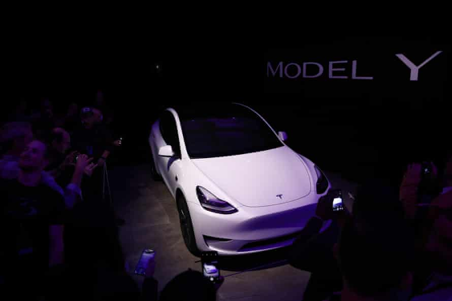 An attendee takes a photograph of the Tesla Inc. Model Y crossover electric vehicle during an unveiling event in Hawthorne, California, U.S.