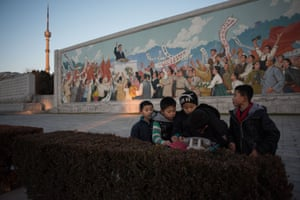 Local children gather after cleaning the area in front of a mosaic near the Kim Il-Sung stadium in Pyongyang