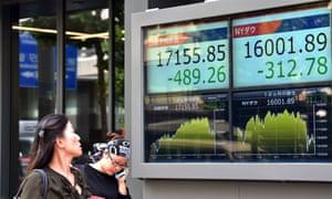 Pedestrians pass a share price board in Tokyo