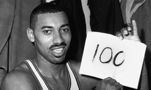 """Wilt Chamberlain of the Philadelphia Warriors holds a sign reading """"100"""" after he scored 100 points in a game in 1962."""