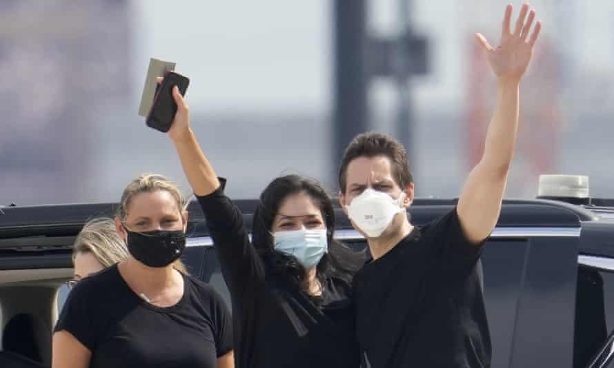 Michael Kovrig waves to the media with his wife and sister after arriving in Toronto's Pearson International Airport on 25 September 2021.