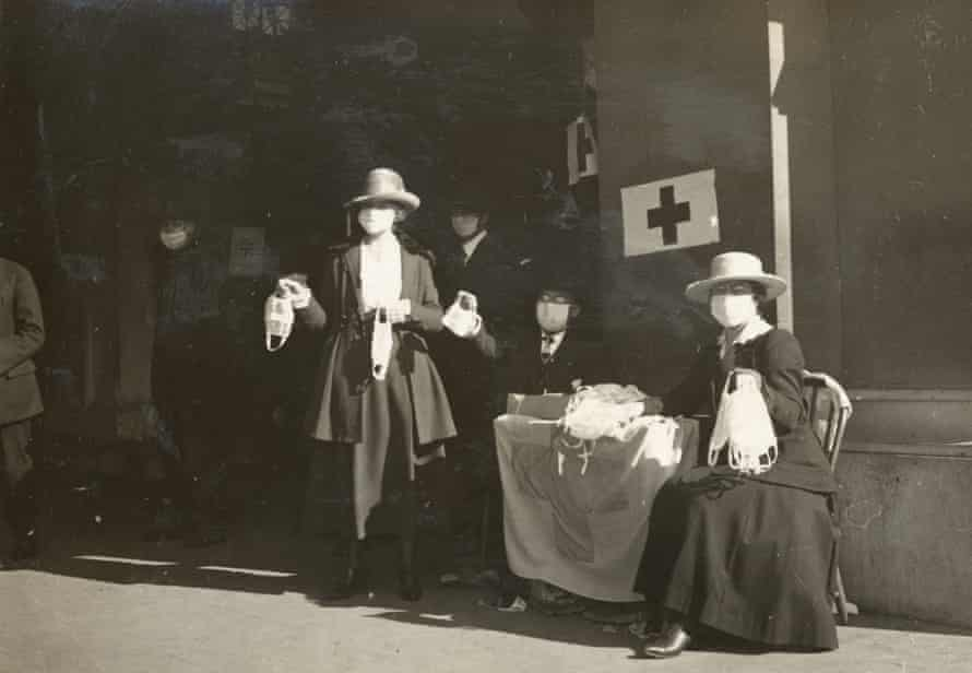 Volunteers with the Red Cross hand out flu masks at a table in San Francisco in 1918.