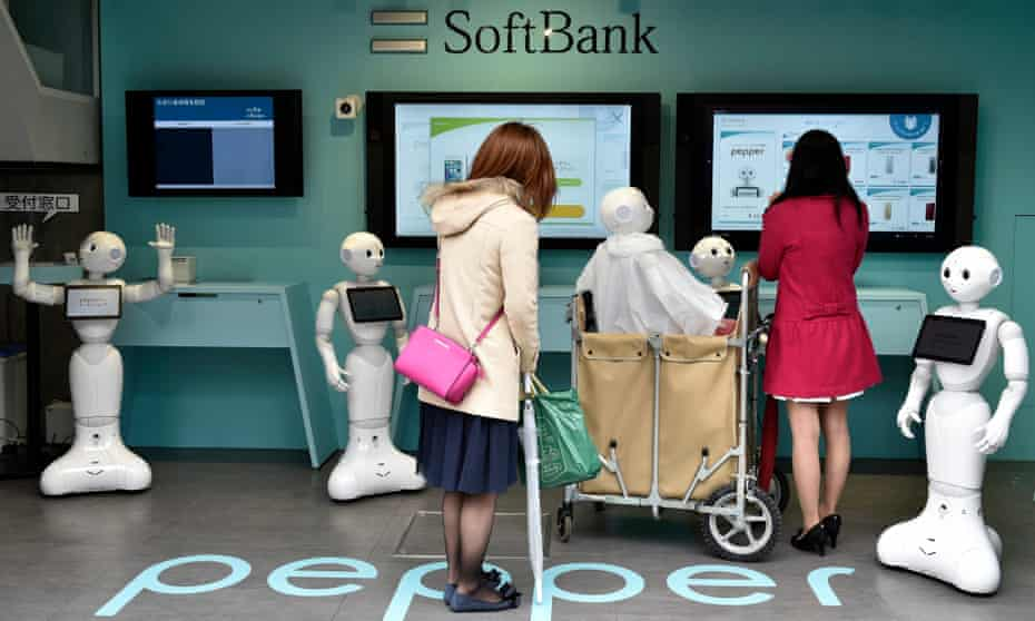 Young women visit a newly opened robot-staffed store where robots welcome customers looking to buy a mobile phone.