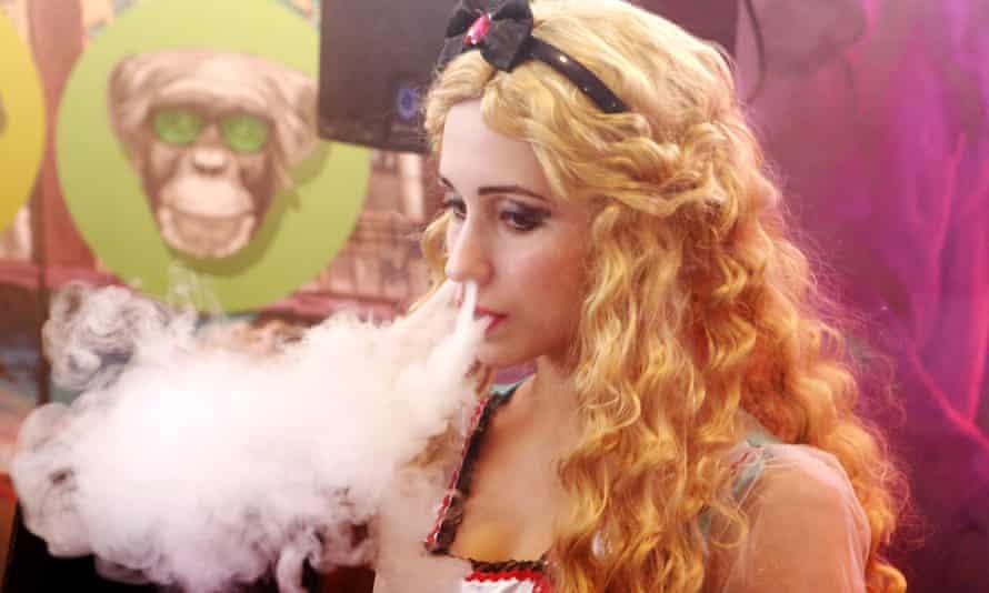 A young woman smokes an electronic cigarette