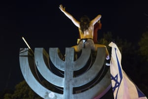 A woman sits on a menorah, part of the Israeli national emblem, during the demonstration