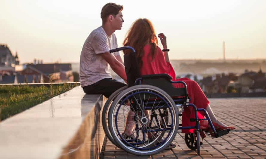 Young man sitting next to young woman in wheel chair