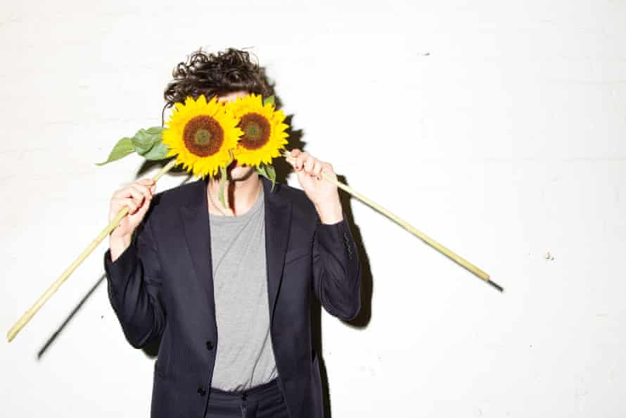 Matt Healy of the band the 1975, holding sunflowers in front of his eyes