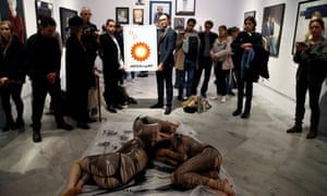 Activists lie on the ground, covered in fake crude oil, to protest BP sponsorship at the National Portrait Gallery.