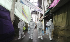 Workers spray disinfectant at a market in Daegu, South Korea on Sunday.
