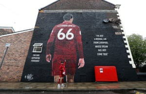 A young fan poses for a picture by a mural of Trent Alexander-Arnold on his was to Anfield where Liverpool took on Norwich City for the first of 380 Premier League games this season.