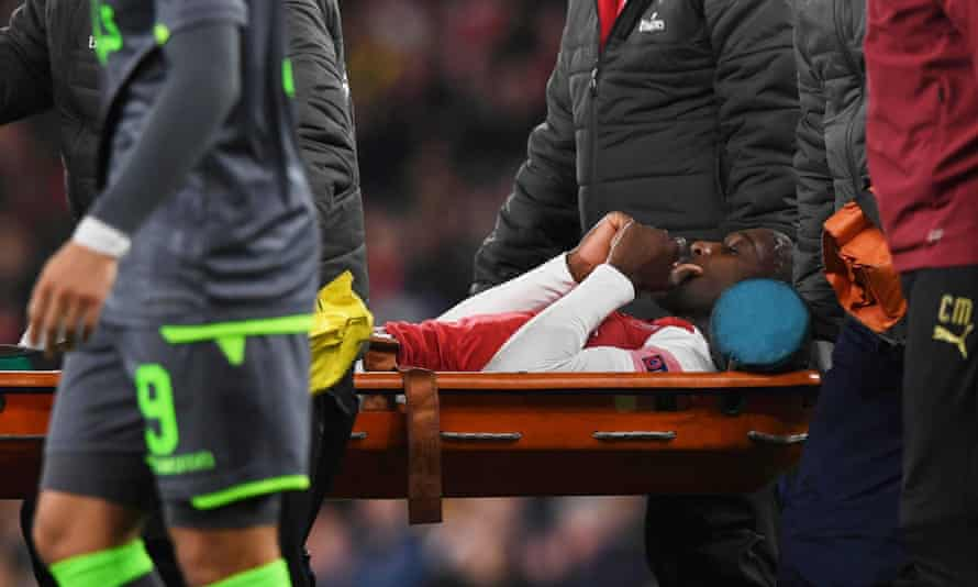 Arsenal's Danny Welbeck is carried off the pitch in the first half after injuring an ankle in the 0-0 draw against Sporting.