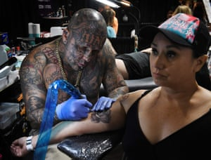 An artist works on a tattoo at the LA Tattoo Convention in Long Beach, California