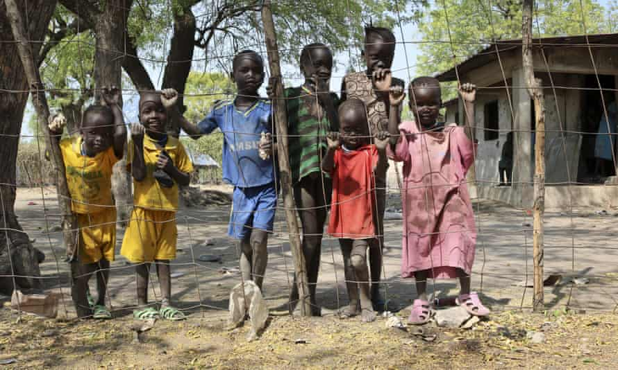 """In this photo taken January 18, 2018, recently displaced children sheltering in a rundown building look through the fence toward the market in Akobo town, one of the last rebel-held strongholds in South Sudan. South Sudan's opposition is threatening to resort to """"guerrilla warfare"""" if peace talks fail"""