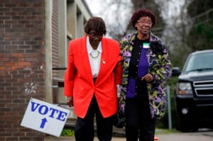 Sadie Janes (L) is assisted by a poll station worker after voting at Floyd Middle Magnet School during the Democratic presidential primary in Montgomery, Alabama on Super Tuesday, March 3, 2020.