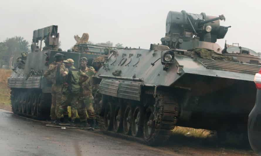 Soldiers stand beside military vehicles just outside Harare