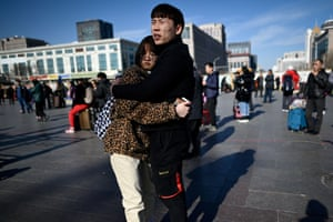 Beijing, China: A couple embrace at the entrance to a train station
