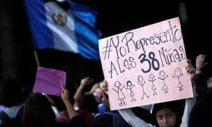 A girl holds a sign reading 'I represent the 38 girls' as protesters outside the national palace in Guatemala City demand justice for the victims of a fire at the Virgen de la Asunción children's shelter