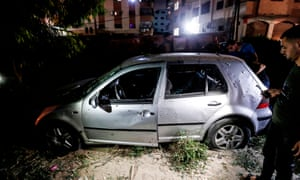 Palestinians look at a damaged car after an explosion near a police checkpoint in Gaza City.