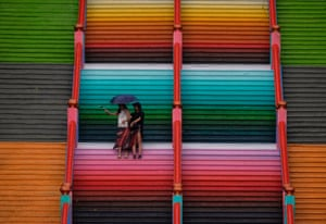 Batu Caves, Malaysia: visitors on the 272-step staircase leading up to the Sri Subramaniar Swamy temple, painted to resemble a rainbow as part of a rejuvenation process performed once every 12 years