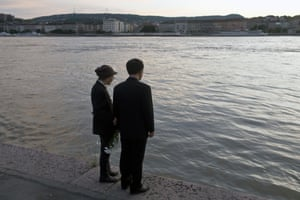 Mourners hold flowers as they stand on the banks of the Danube river where a sightseeing boat had capsized