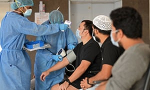 Health workers take the temperatures of migrant workers in Dubai in April