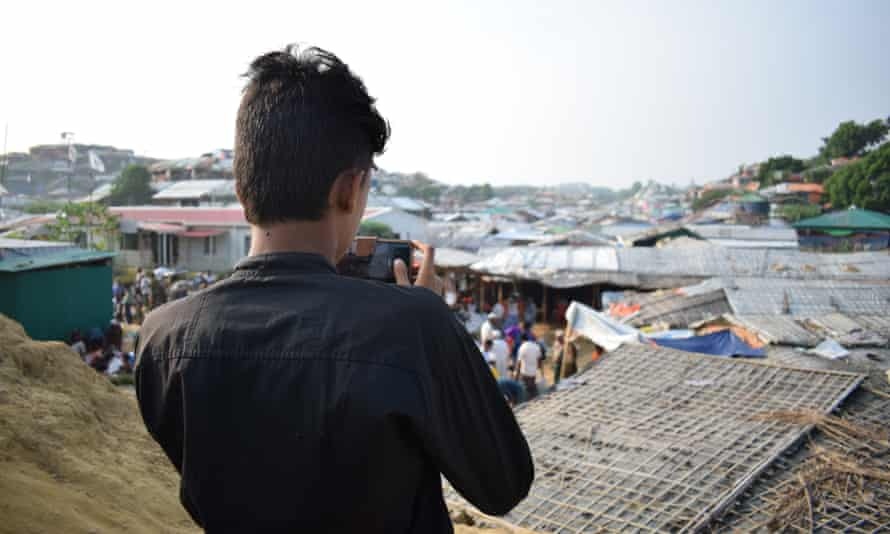 Azimul Hassan holding his camera overlooking the refugee camp.