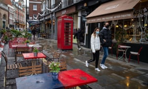 People wearing face masks walk pass empty tables outside bars and restaurants in Covent Garden, in central London