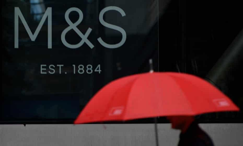 a man with a red umbrella passes an M&S branch