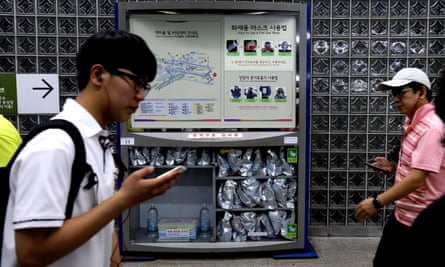 Commuters walk past a case of gas masks and other emergency equipment in a metro station in Seoul, South Korea.