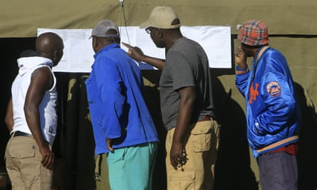 People look at results placed outside a polling station in Harare
