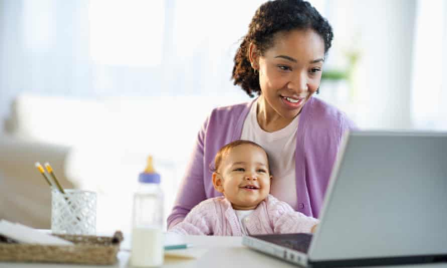 A woman holds a baby while using a laptop.